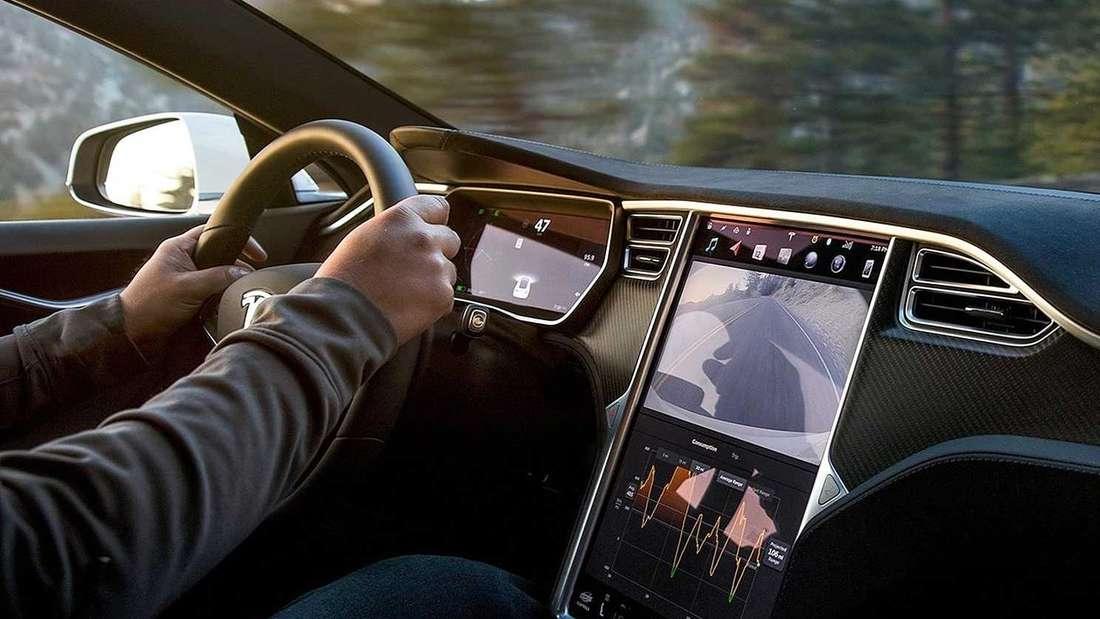 Ein Fahrer am Steuer eines Tesla Model S