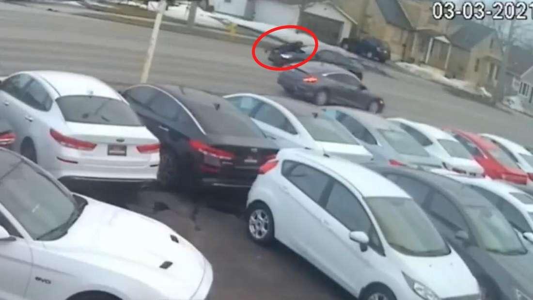 Autoverkäufer krallt sich an Motorhaube eines BMW M4 fest.