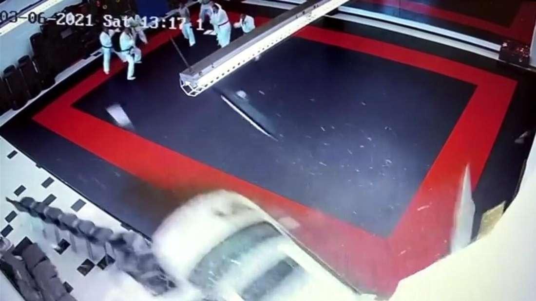 Eine weiße Limousine bricht durch die Wand einer Kampfsportschule.
