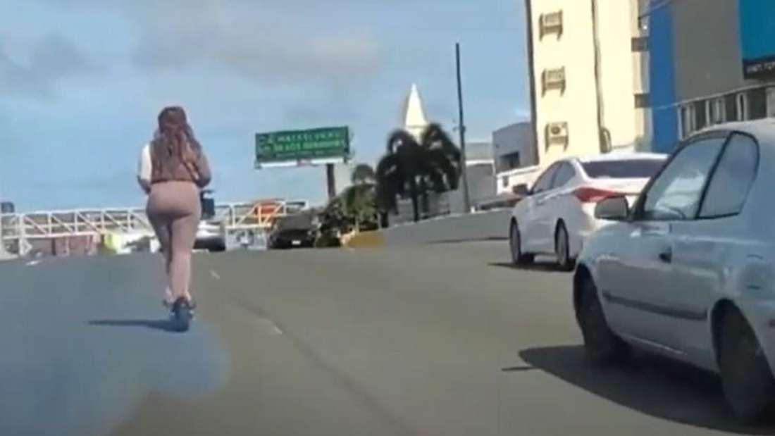 Eine Frau fährt auf einem E-Scooter auf einer Autobahn.