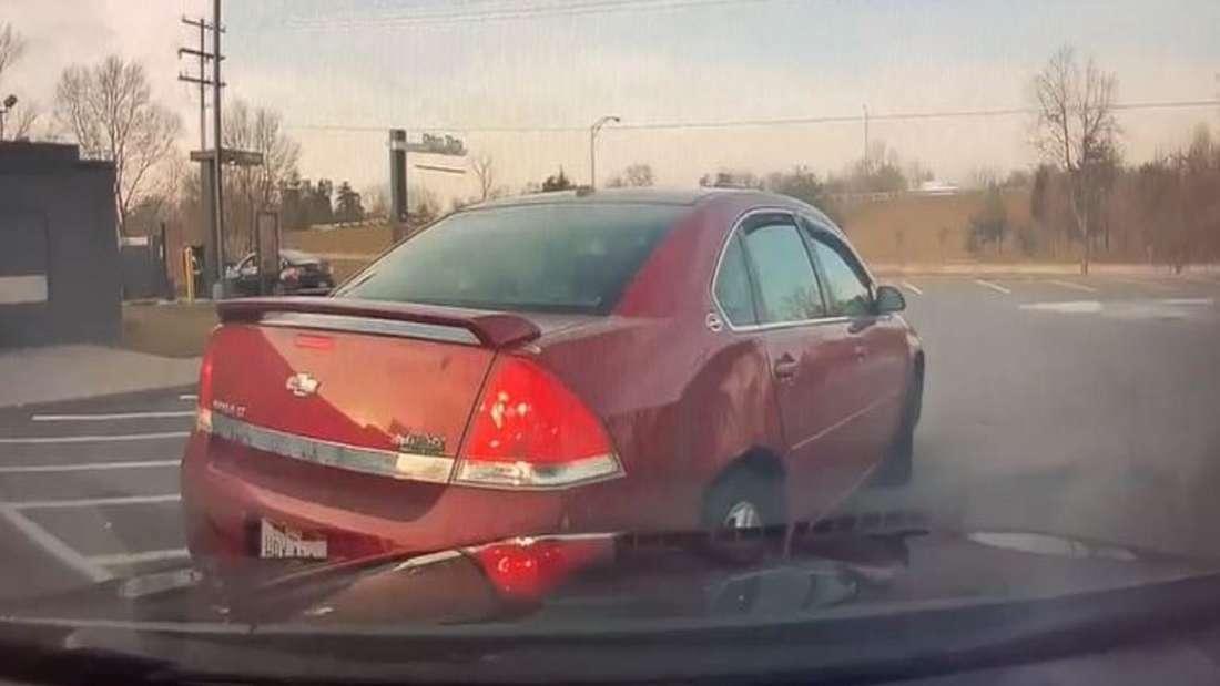 Ein dunkelroter Chevrolet wird mit der Dashcam gefilmt, wie er rückwärts einen Wagen rammt.