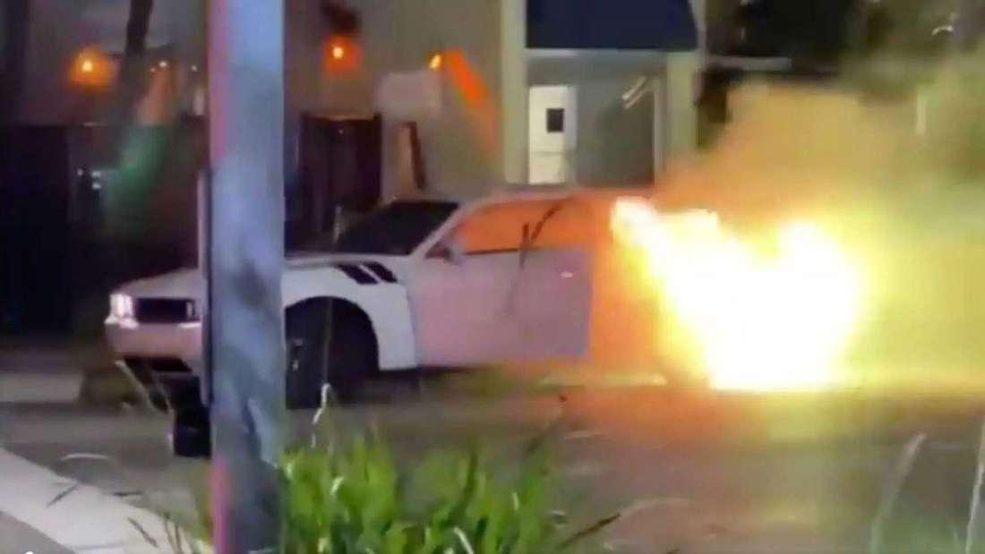 Ein weißer Dodge Challenger geht auf der Straße in Flammen auf.