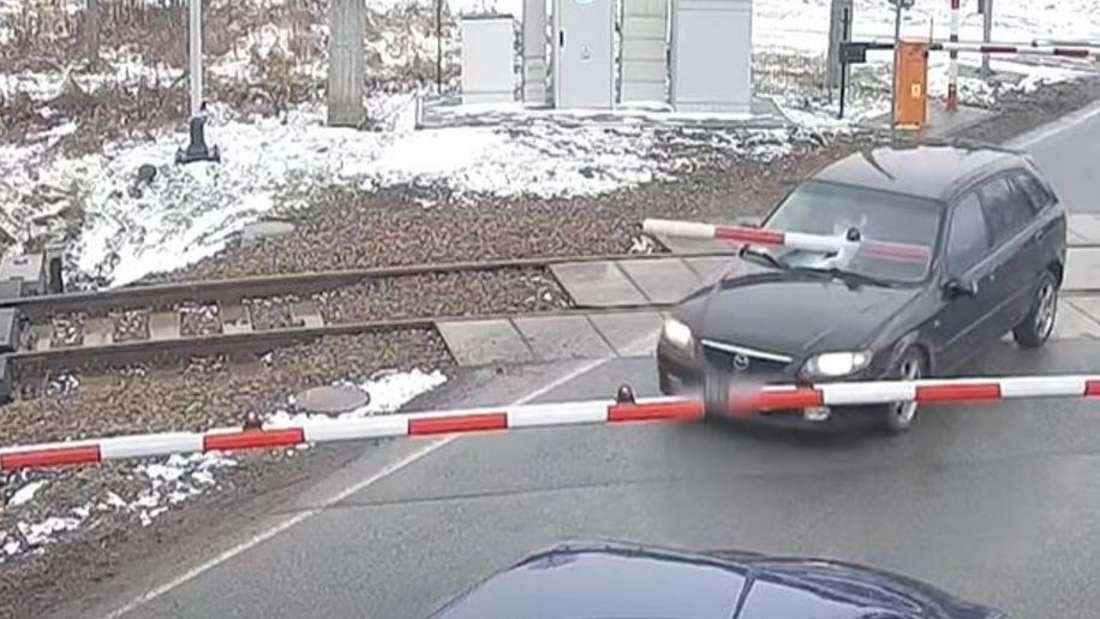 Mehrere Autos stehen an einem Bahnübergang. Eine Schranke bohrt sich in die Windschutzscheibe eines Mazda.