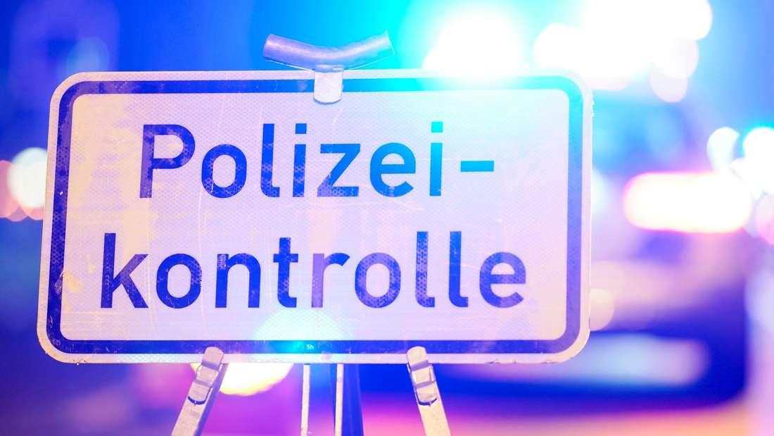 """Ein Schild mit der Aufschrift """"Polizeikontrolle"""" bei einer Kontrolle von Autofahrern (Symbolbild)"""