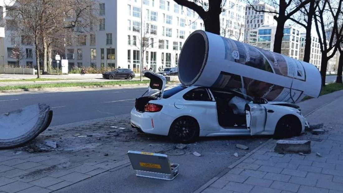 Ein weißer BMW M2 ist unter einer umgefallenen Litfaßsäule eingeklemmt.