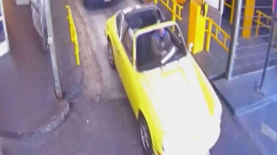 Ein gelber Porsche 911 kommt aus einem Parkhaus gefahren.