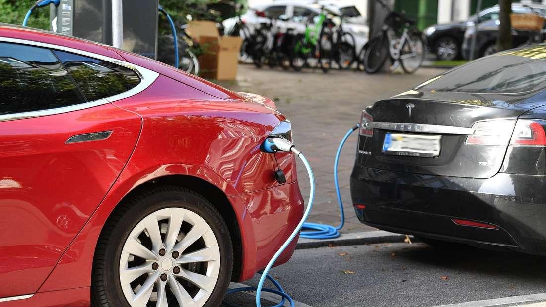 Zwei E-Autos von Tesla werden an Ladesäulen aufgeladen. (Symbolbild)