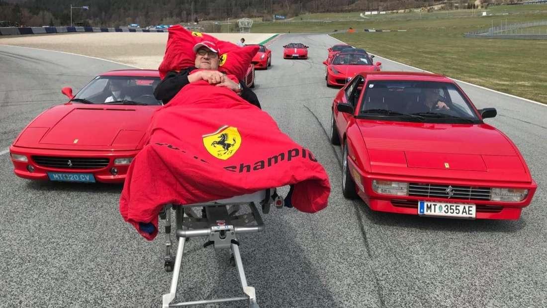 Mitte: Jürgen (50) auf einer Liege mit Ferrari-Decke. Dahinter: acht Ferraris.