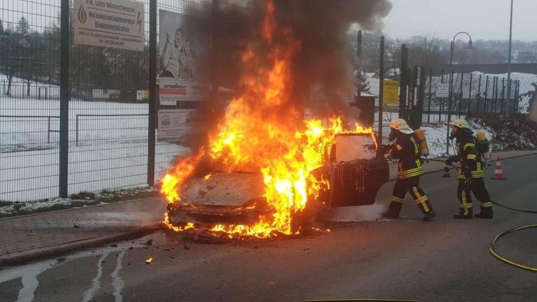 Ein Ford steht in Flammen, Einsatzkräfte versuchen den Brand zu löschen.