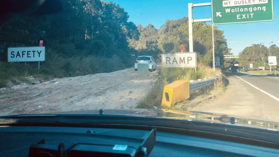 Ein weißer Mitsubishi steht mitten auf einer Notfallspur neben einem Highway.