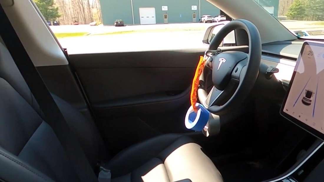 Blick auf den leeren Fahrersitz eines Tesla mit geschlossenem Gurt und Gewicht am Lenkrad