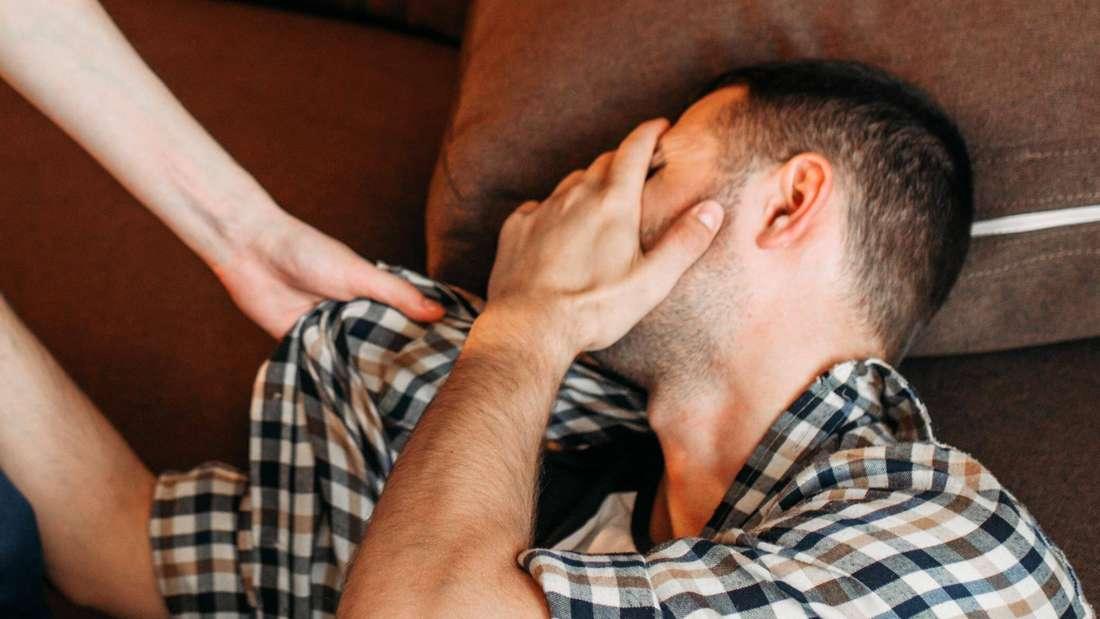 Ein Mann hält sich die Hand vors Gesicht, eine Frau packt ihn am Kragen (Symbolbild)