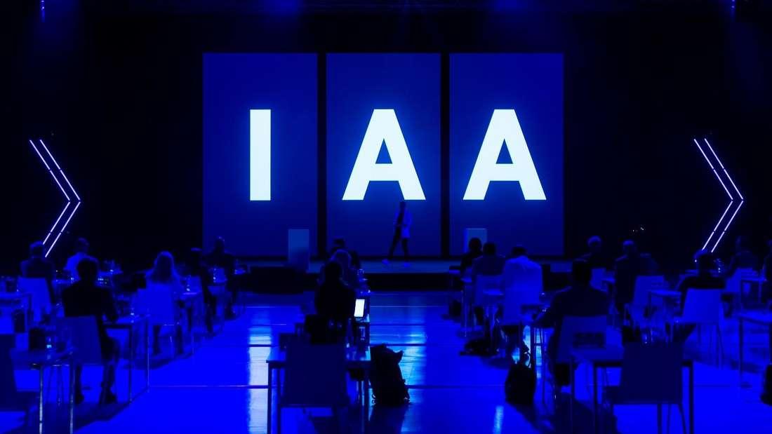 """Die Buchstabenkombination IAA leuchtet auf drei Bildschirmen einer Pressekonferenz der Internationalen Automobil-Ausstellung """"IAA Mobility 2021""""."""