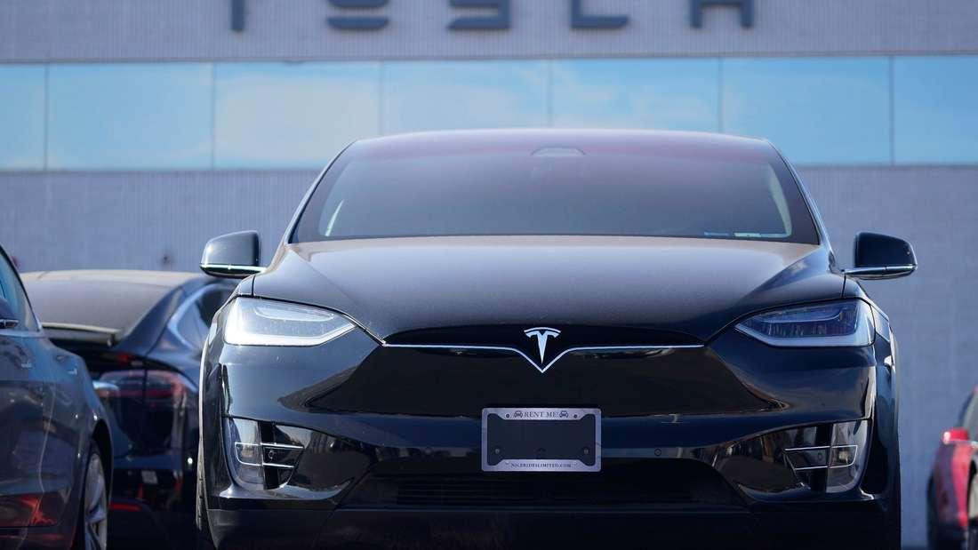 Ein Tesla Model X SUV steht vor dem Gebäude eines Tesla-Händlers.