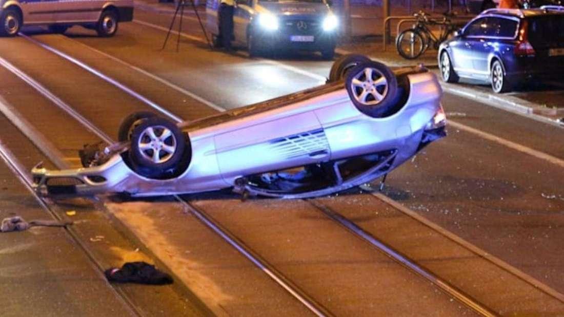 Ein silberner Mercedes liegt auf dem Autodach auf Straßenbahngleisen.