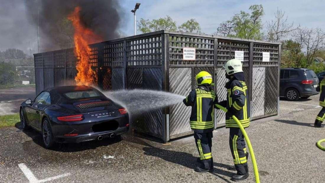Die Feuerwehrleute löschen den Brand am Porsche 911 Carrera S.