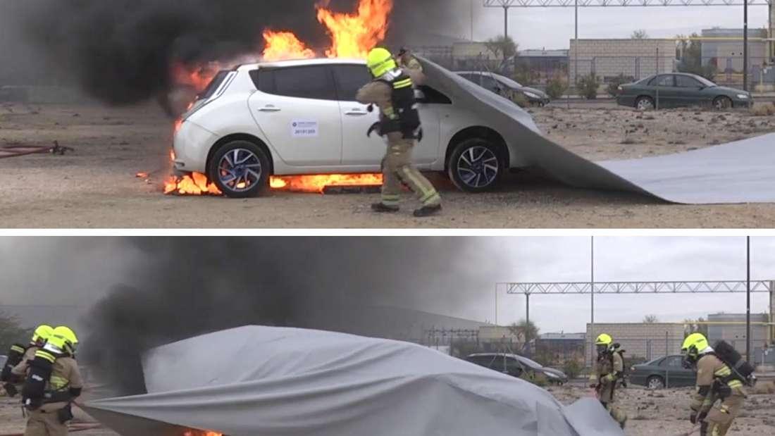 Feuerwehrmänner ziehen eine Löschdecke über ein brennendes Auto
