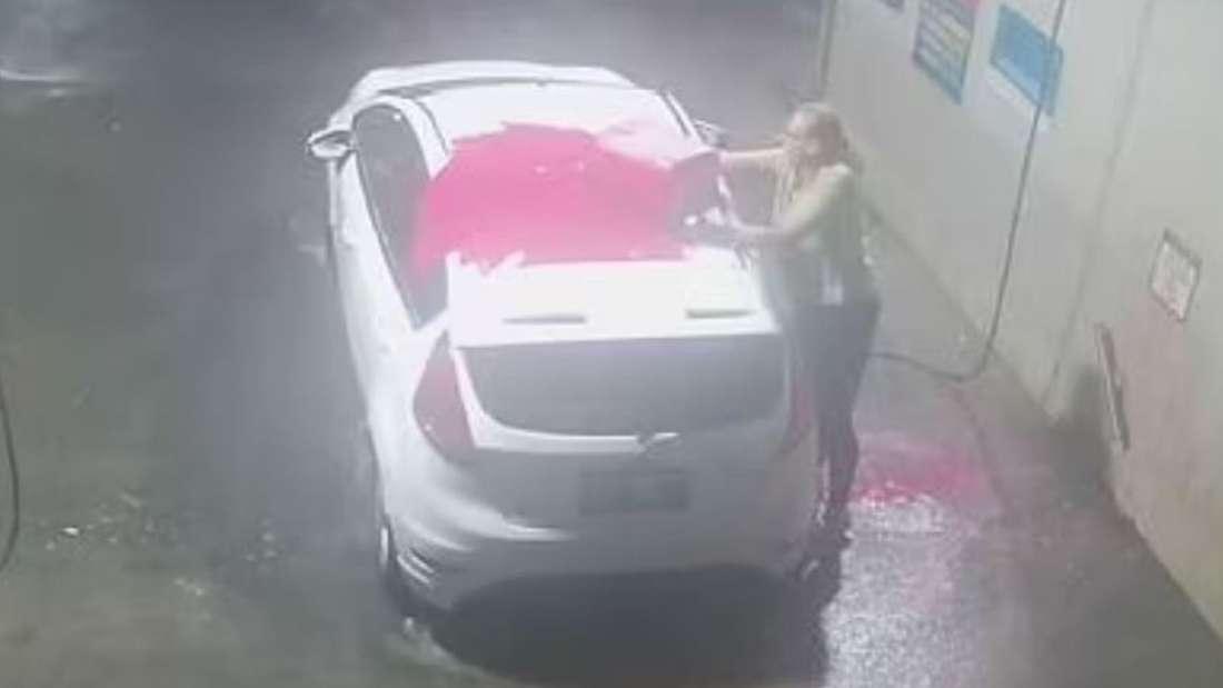 Eine Frau schrubbt ihre weiße Kombilimousine mit einer pinken Reinigungssubstanz.