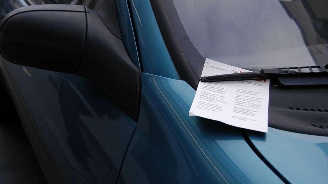 Ein Zettel ist unter dem Front-Scheibenwischer eines Autos festgeklemmt. (Symbolbild)