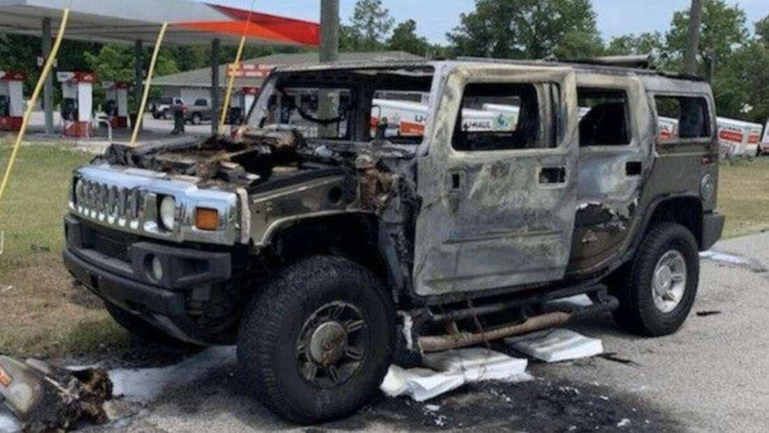 Ein völlig ausgebrannter Hummer Geländewagen steht vor einer Tankstelle.