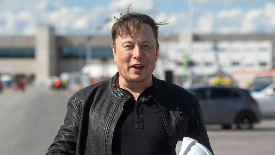 Tesla-Chef Elon Musk auf der Baustelle der Tesla Gigafactory in Grünheide mit Schutzhelm im Arm.
