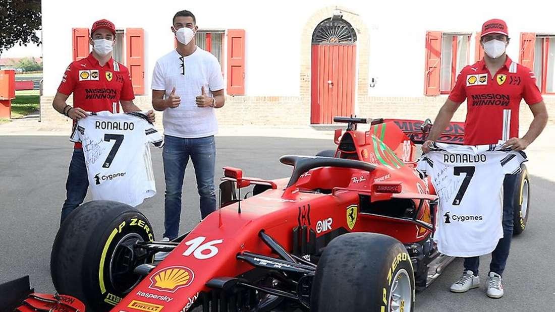 Fußballer Cristiano Ronaldo mit Formel-1-Fahrern Sainz und Leclerc am Rennwagen