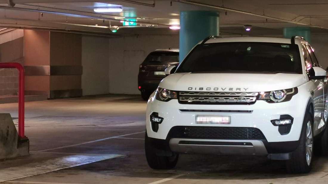 Ein weißer Land Rover Discovery parkt über zwei Stellplätze.