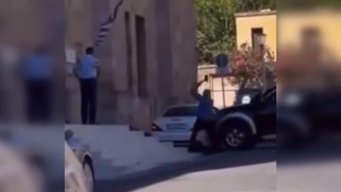 Ein Mann steigt aus seinem Mitsubishi L200-Pick-up und drischt mit einem Vorschlaghammer auf einen Mercedes SL ein.