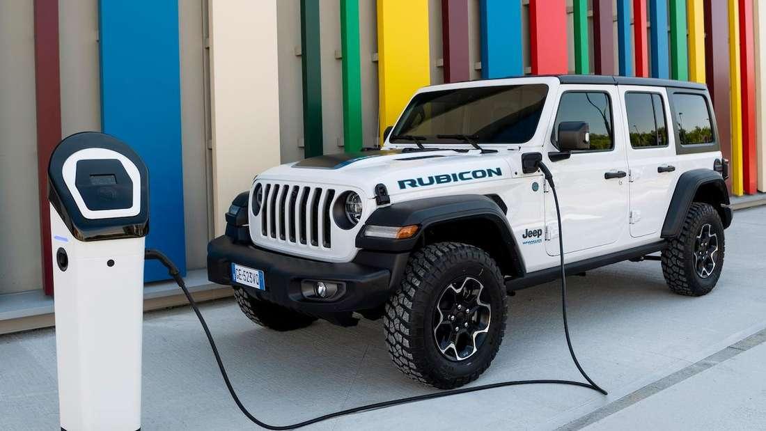 Der Plug-in-Hybrid Jeep Wrangler Unlimited 4xe PHEV lädt vor einer bunten Wand an einer Ladesäule.