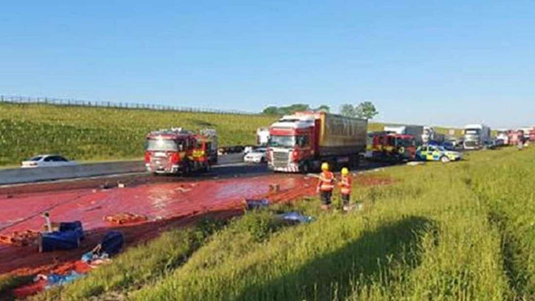 Ein Lkw mit Tomatenmark kippt auf einer britischer Autobahn um.