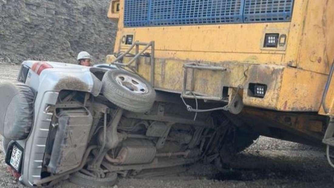 Ein Kipplaster überrollt halb einen Suzuki-SUV.