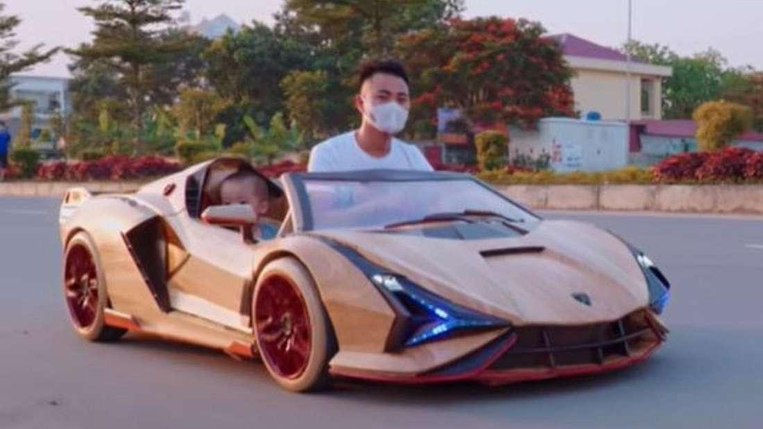 Der YouTube-Bastler fährt mit seinem Sohn im Holz-Lamborghini eine Straße entlang.