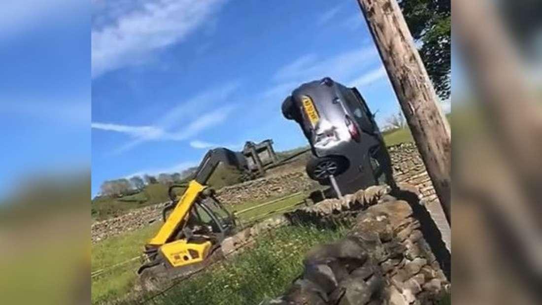Ein Traktorfahrer nimmt einen Pkw auf seine Gabel und hebt ihn in die Höhe, während der Besitzer zusieht.