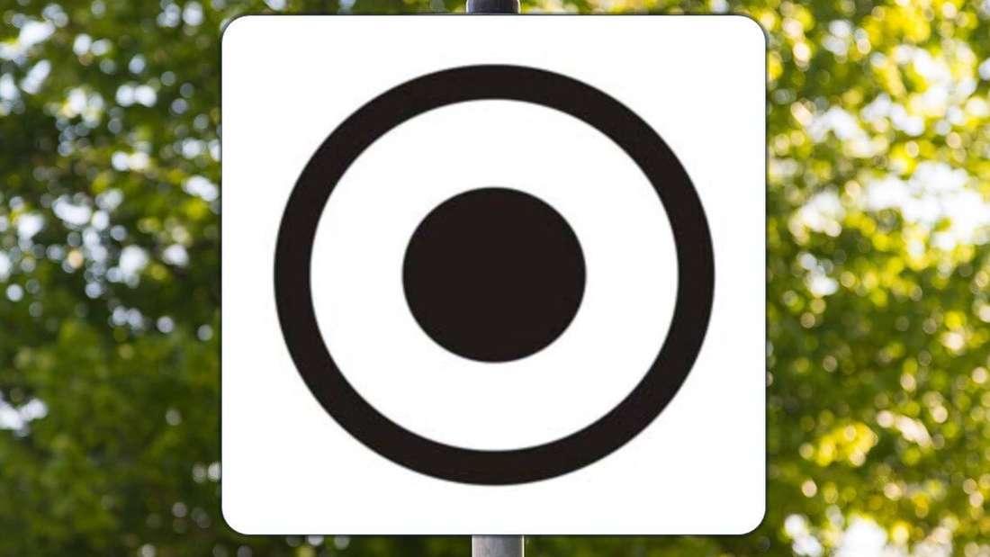 Ein Verkehrsschild mit schwarzem Punkt in schwarzem Kreis (Montage)