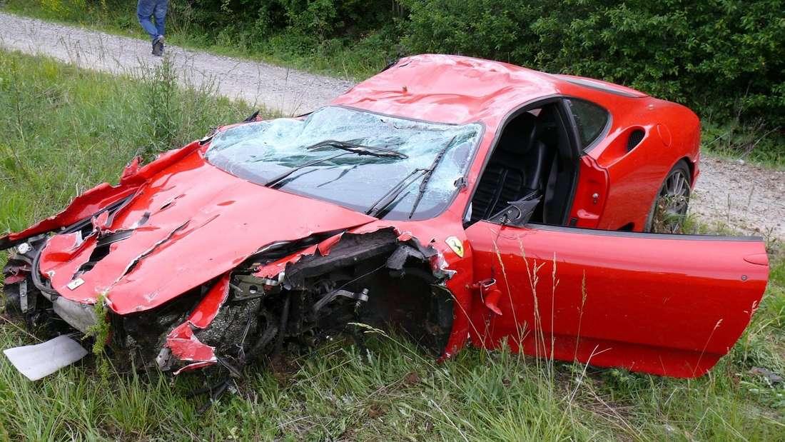 Verunfallter Ferrari, das Fahrzeugwrack liegt am Rande einer Straße in der Böschung. (Symbolbild)