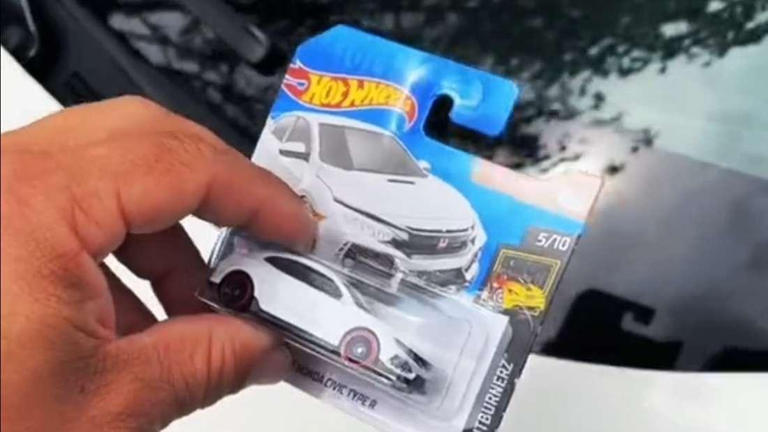 """Eine Hand legt ein """"Hot Wheels""""-Modellauto auf ein echtes Auto."""