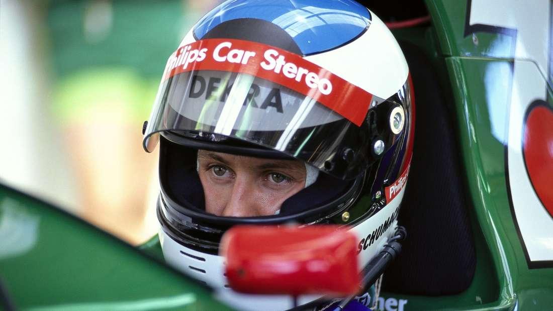 Michael Schumacher sitzt im Rennwagen und trägt einen Helm mit geöffnetem Visier.