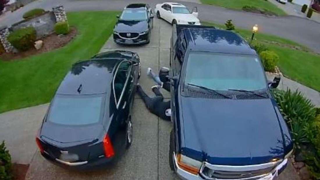 Zwei Männer machen sich an einem Ford Pick-up zu schaffen und entfernen den Katalysator.