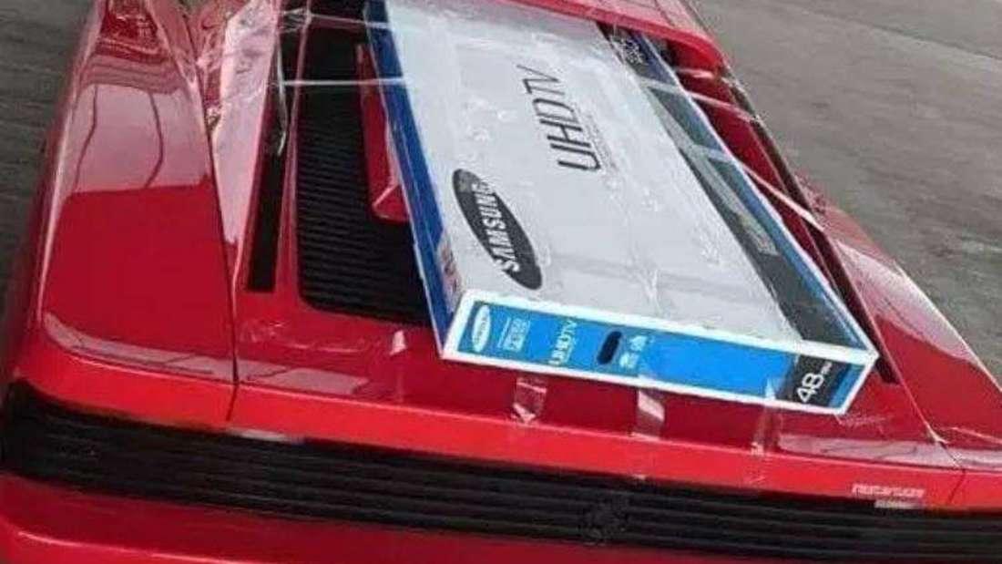 Ein Ferrari Testarossa transportiert einen Flachbild-Fernseher.