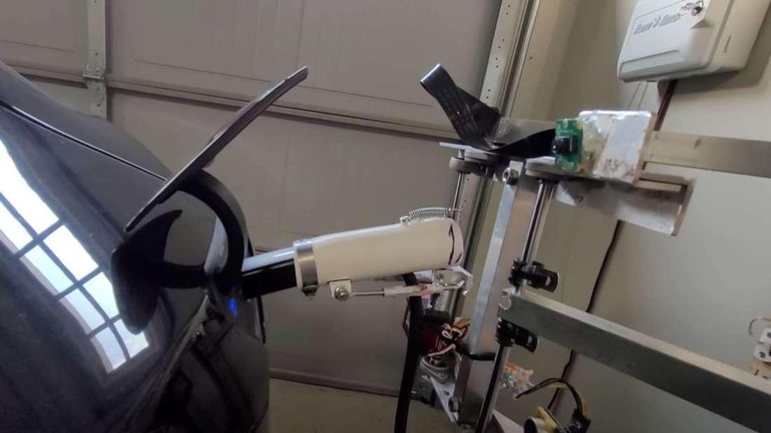 Der Ladearm des von Pat Larson gebauten Lade-Roboters für Tesla Modelle steckt in der Ladebuchse eines Tesla Model 3.