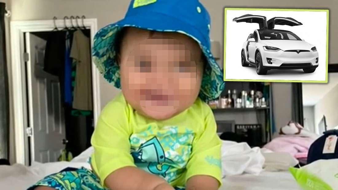 Ein Baby sitzt auf einem Bett und hält eine Milchflasche, als Einklinker ist das Tesla Model X zu sehen. (Symbolbild)