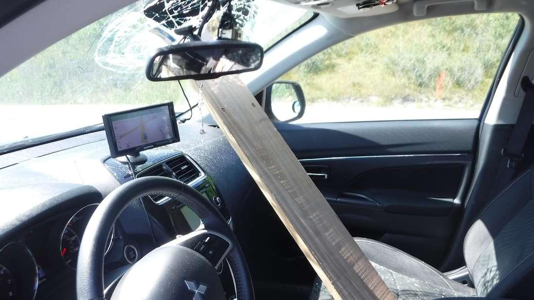 Eine lange Holzlatte hat die Windschutzscheibe des Mitsubishi Outlander durchbohrt und ragt bis in den Innenraum.