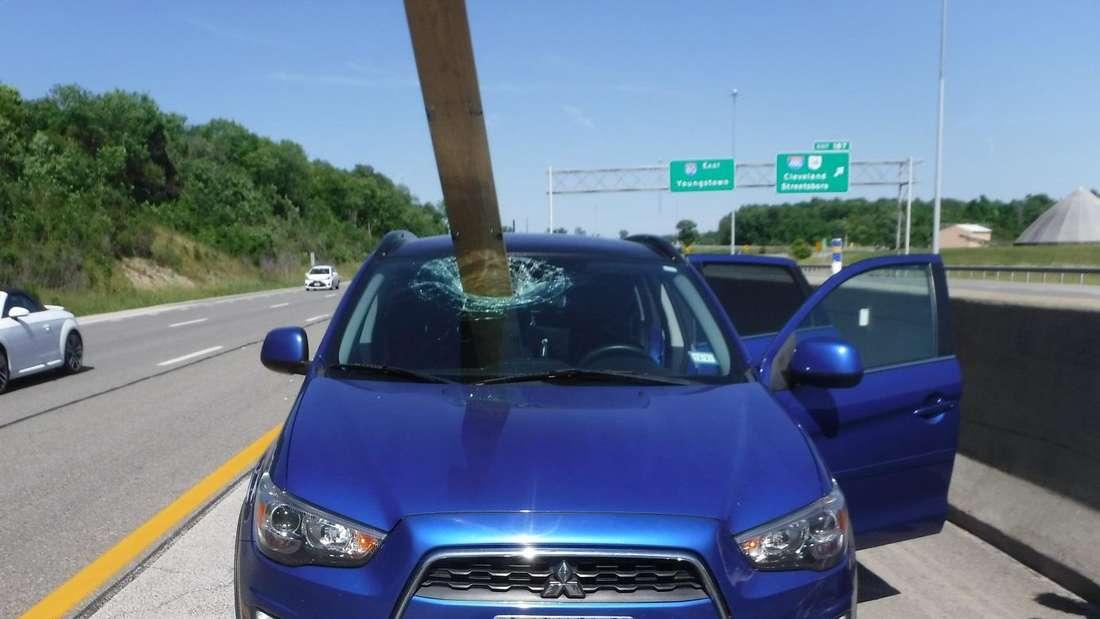 Eine lange Holzlatte steckt in der Windschutzscheibe eines blauen Mitsubishi Outlanders.