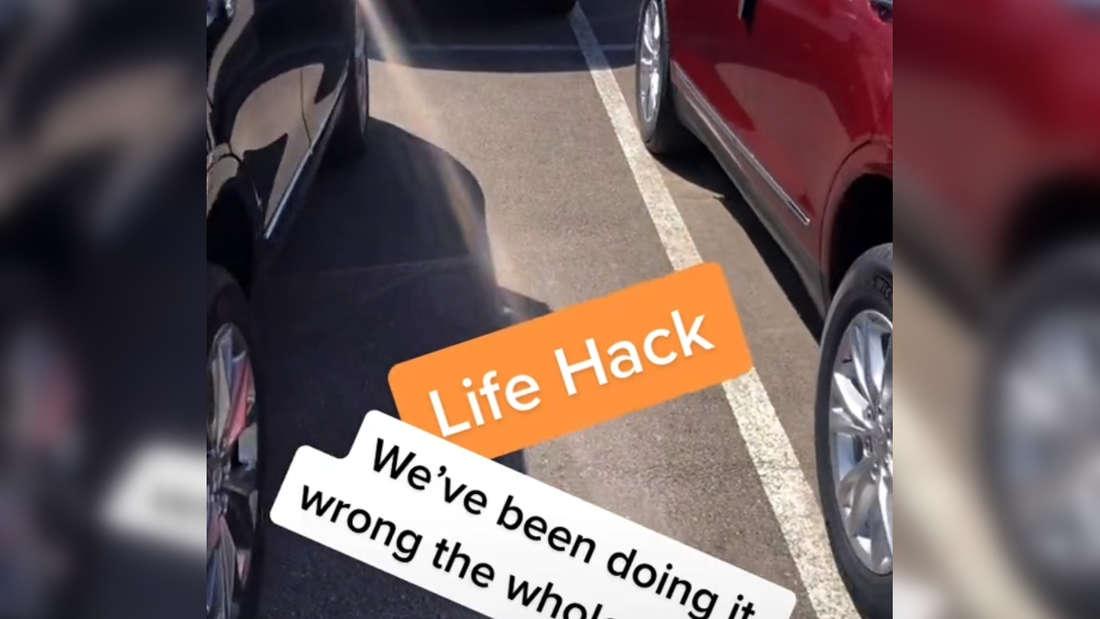 Autos parken auf einem Parkplatz und stehen alle auf der linken Markierungslinie.