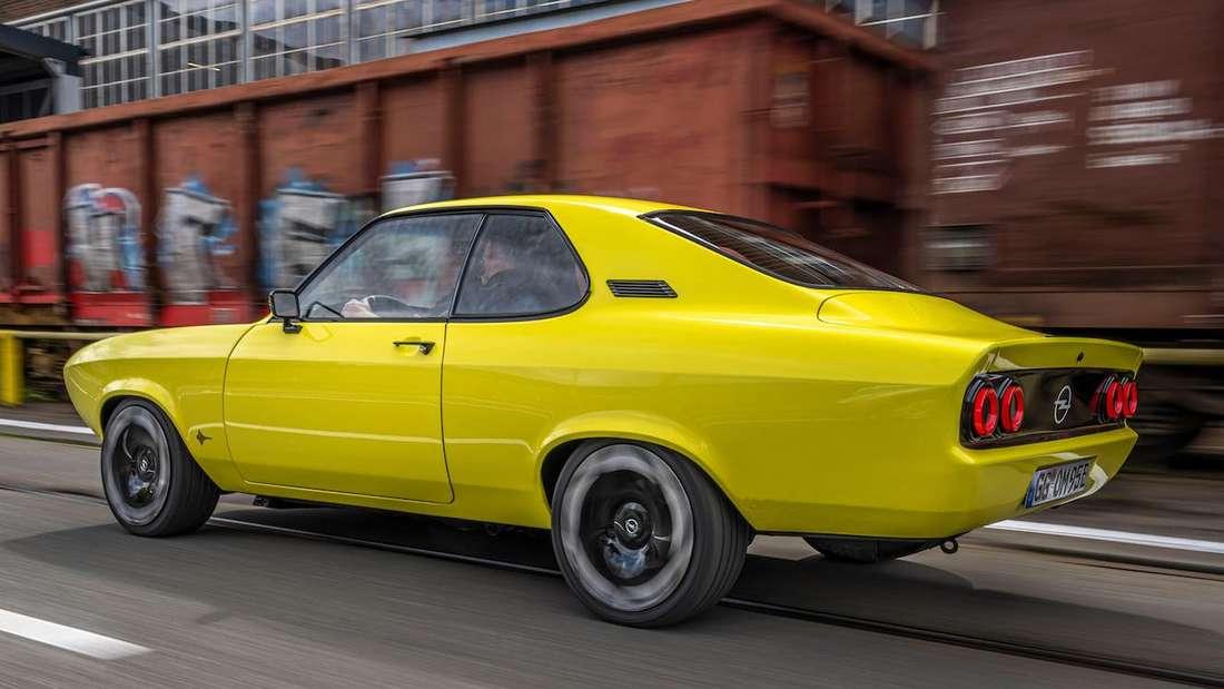 Ein knallgelber, vollelektrischer Opel Manta von links hinten