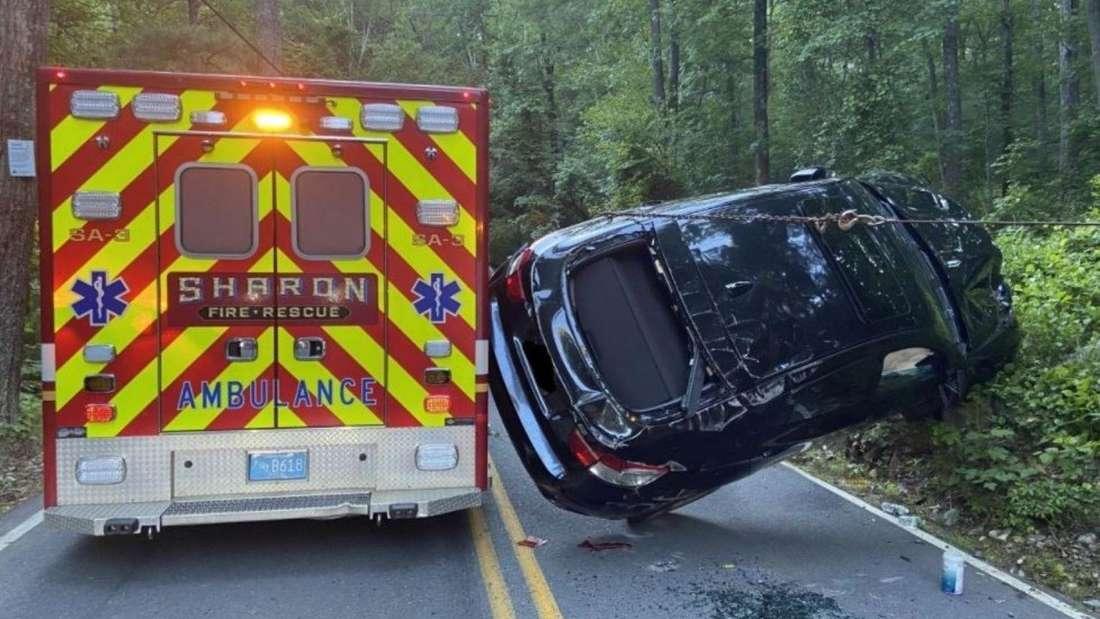Ein BMW X6 lehnt auf dem Hinterrad nach Unfall mit Rettungswagen.