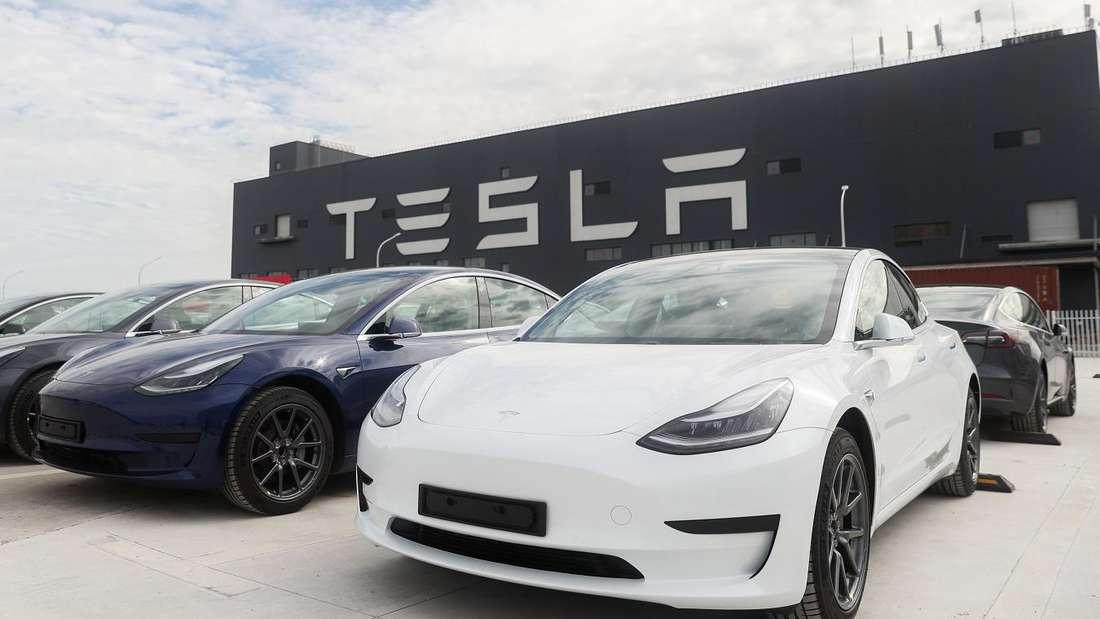 Mehrere Tesla Model 3 stehen vor einer Tesla Gigafactory Autofabrik.