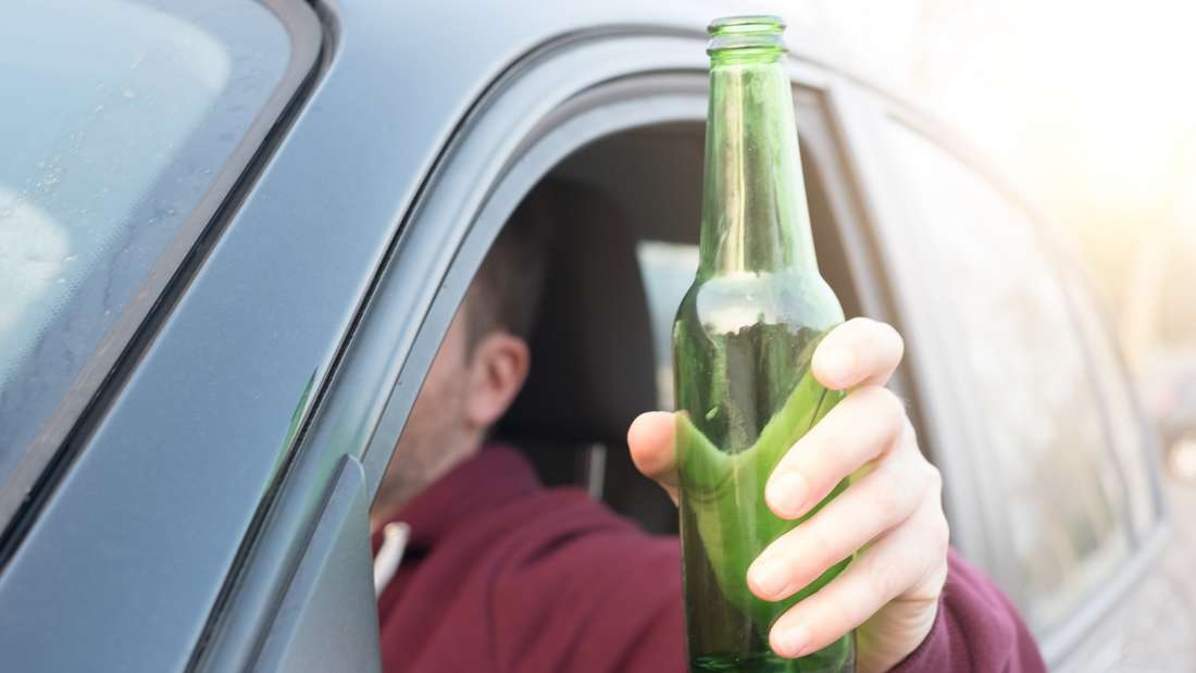 Ein Autofahrer betrinkt sich am Steuer eines Wagens. (Symbolbild)