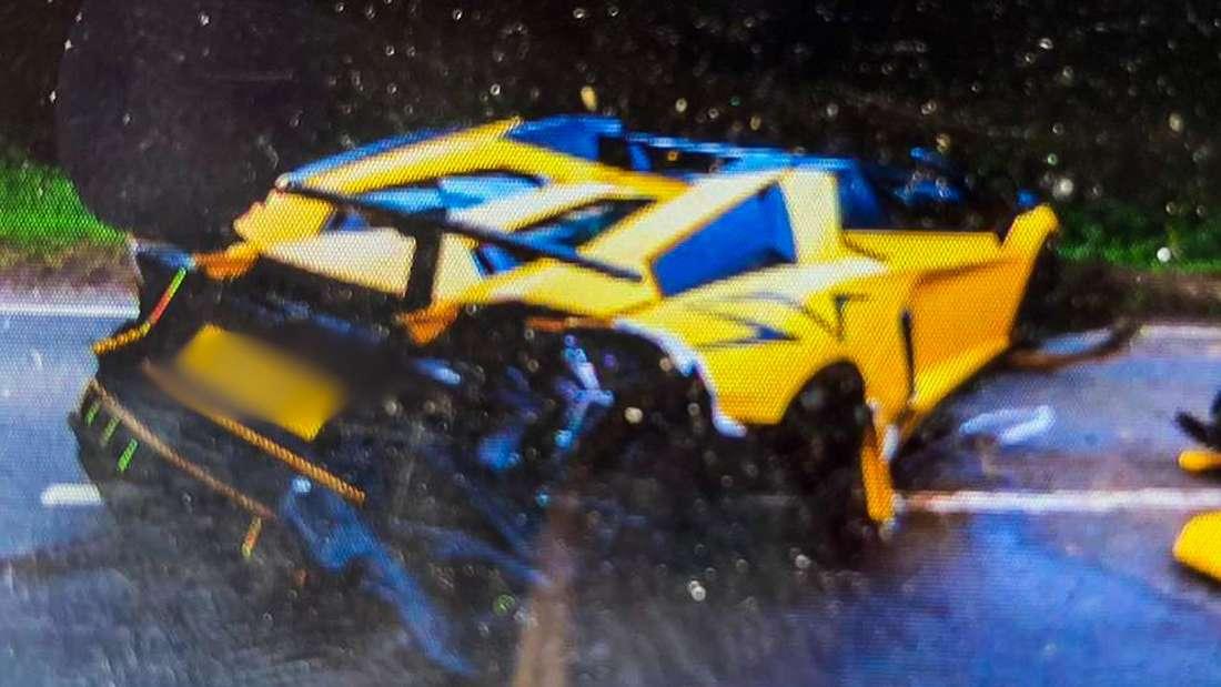 Ein gelber Lamborghini Aventador liegt als Wrack auf der Straße.