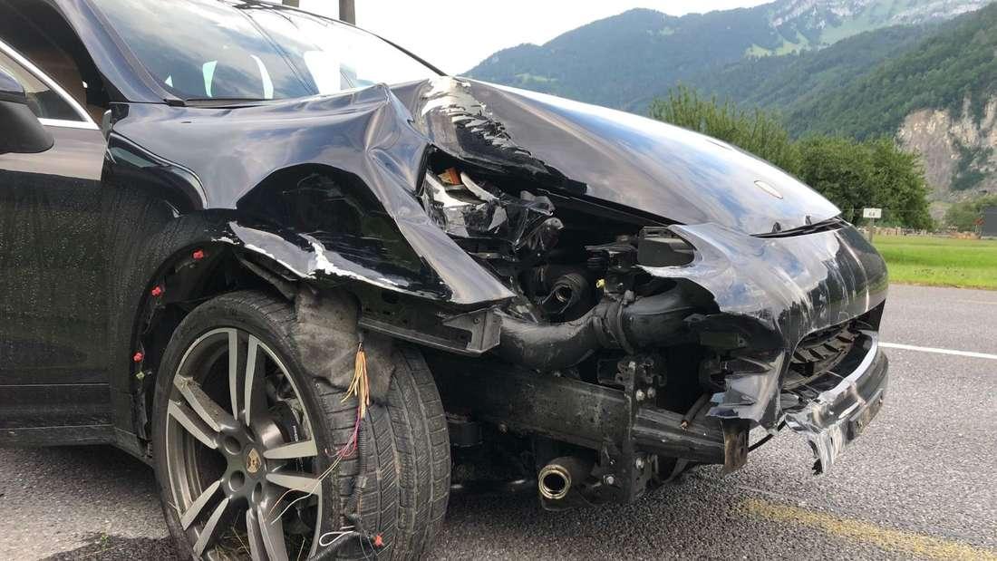Ein schwarzer Porsche ist nach einem Zusammenprall ein Totalschaden.